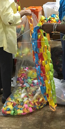 Hobby team members assemble part of the prayer chain that will brighten the walls of the community room in the prison.